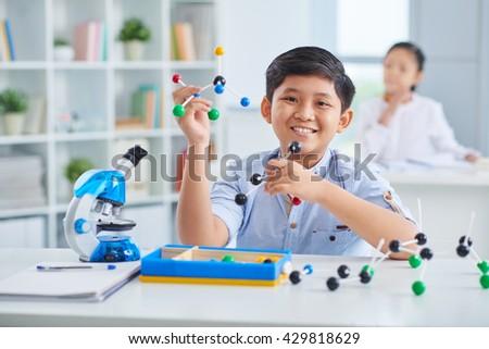 Cheerful Asian boy making molecular model in class - stock photo