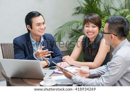 Cheerful Asian business partners having meeting in restaurant
