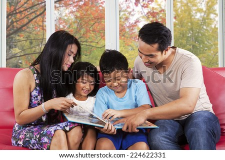 Cheerful asian children read a story book with their parents at home in autumn day - stock photo