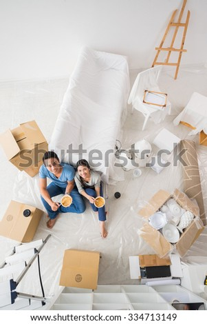 Cheerful Asian couple looking at the camera when eating in their new house, view from the top - stock photo