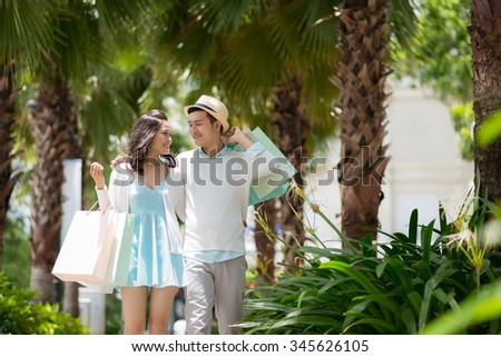 Cheerful Asian couple with paper bags walking outdoors - stock photo
