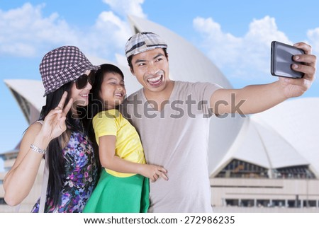 Cheerful asian family enjoying holiday by taking self portrait at Opera House in Sydney - stock photo