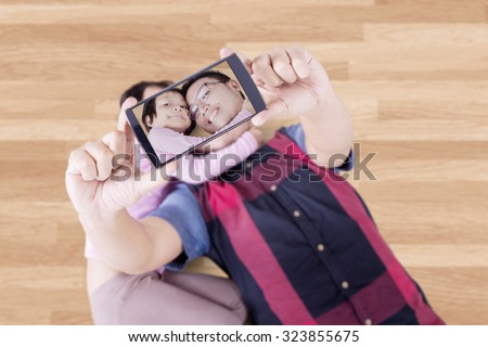 Cheerful asian father and his daughter lying on the floor while taking selfie photo with a smartphone - stock photo