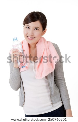 Cheerful Asian girl holding bottle of water, closeup portrait with towel on shoulder on white background. - stock photo