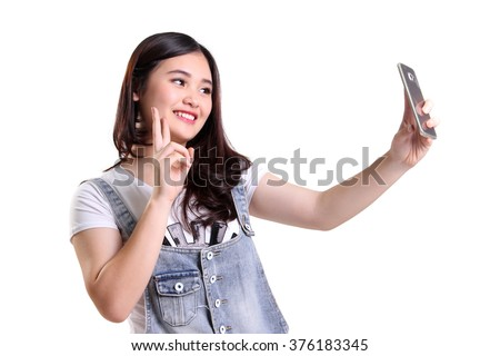 Cheerful Asian girl taking selfie with her smartphone camera and making victory hand sign, isolated on white background - stock photo