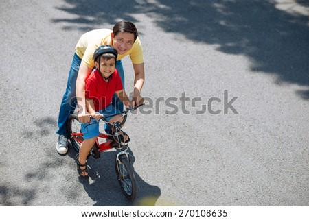 Cheerful Asian kid and his father riding a bike - stock photo