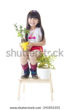 Cheerful asian kid holding pot plant - stock photo