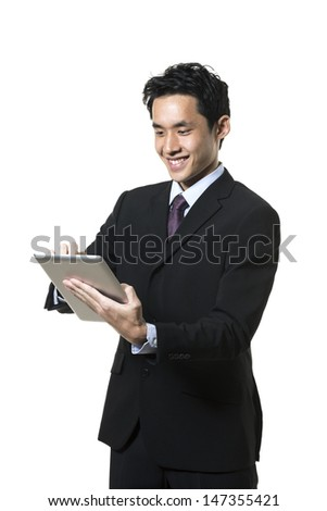 Cheerful Asian man using a tablet PC. Isolated on white background. - stock photo