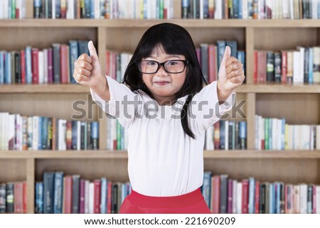 Cheerful asian schoolgirl showing thumbs up in library - stock photo