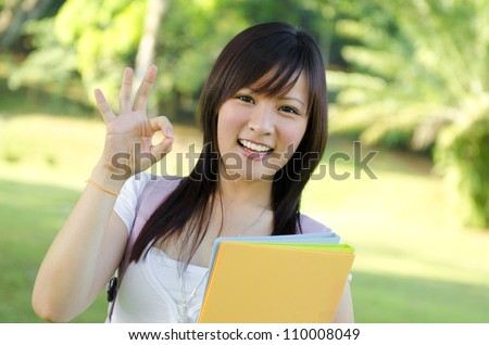 Cheerful Asian university student giving an okay hand sign - stock photo