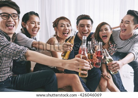 Cheerful Asian young people clinking bottles of beer