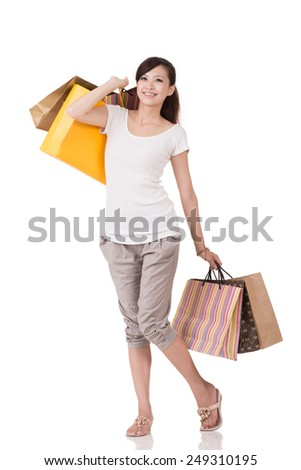 Cheerful Asian young woman shopping and holding bags, full length portrait on white background. - stock photo