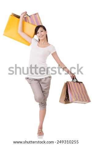 Cheerful Asian young woman shopping and holding bags, full length portrait on white background.
