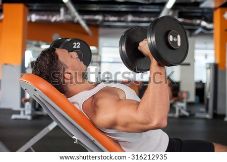 Cheerful athlete is lying on bench in gym. He is raising two dumbbells with efforts