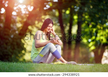 Cheerful athletic woman sitting resting after exercise in the park on the green grass with phone and headphones - stock photo