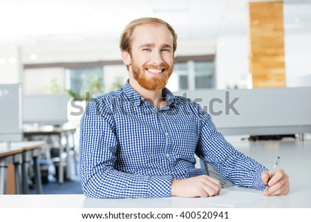Cheerful attractive bearded businessman sitting at the table and writing