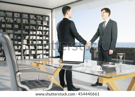 Cheerful attractive businessmen shaking hands in office with blank white laptop, coffee cup and other items on glass desktop. Window with ocean view in the background. Mock up, 3D Rendering - stock photo