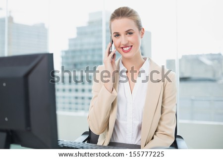 Cheerful attractive businesswoman on the phone in bright office - stock photo