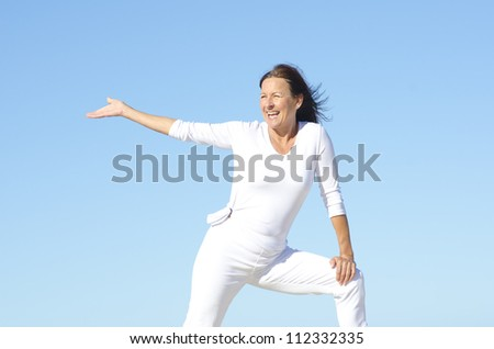Cheerful attractive senior woman being happy and active, isolated with blue sky as background and copy space - stock photo