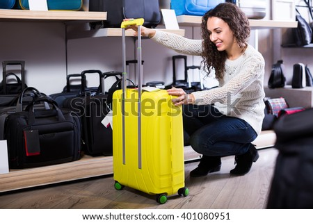 Cheerful attractive woman selecting handy trunk in store and smiling