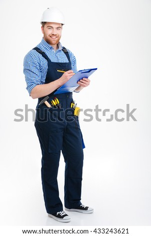 Cheerful attractive young builder standing and writing on clipboard - stock photo