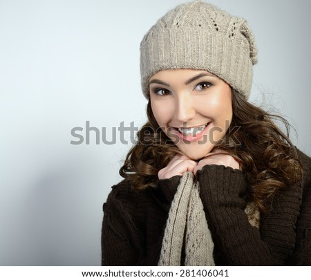 Cheerful attractive young girl smiling and looking at camera, in warm clothes and hat