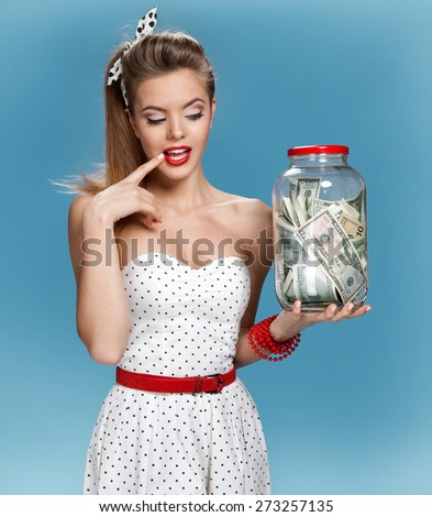 Cheerful attractive young lady holding cash and happy smiling. Shopping concept / photo set of young American pin-up model on blue background - stock photo