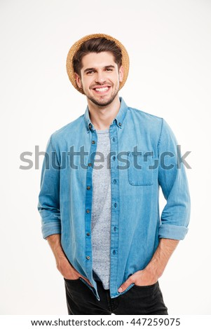 Cheerful attractive young man in hat standing with hands in pockets over white background - stock photo