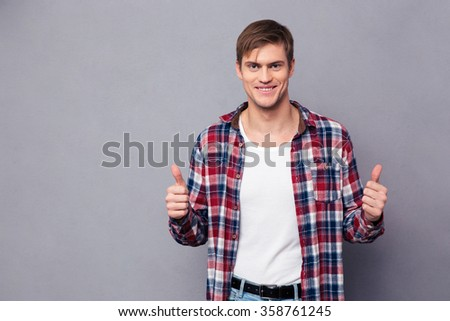 Cheerful attractive young man in plaid shirt showing thumbs up over grey background - stock photo