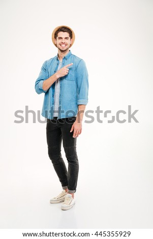 Cheerful attractive young man in plaid shirt standing and pointing away over white background - stock photo