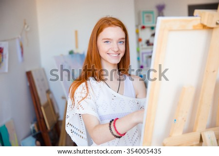 Cheerful attractive young woman artist with red hair painting on canvas in art workshop - stock photo