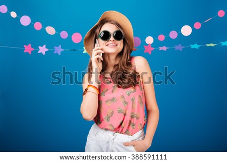 Cheerful attractive young woman in hat and sunglasses talking on mobile phone over blue background - stock photo