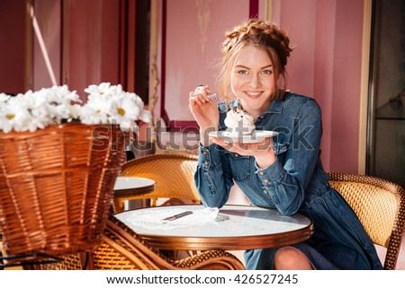 Cheerful attractive young woman smiling and eating cupcake in outdoor cafe - stock photo