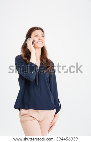 Cheerful attractive young woman standing and talking on cell phone over white background - stock photo