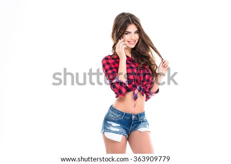 Cheerful attractive young woman standing and talking on mobile phone over white background - stock photo