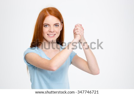 Cheerful attractive young woman with long red hair showing gesture of support with her hands over white background - stock photo