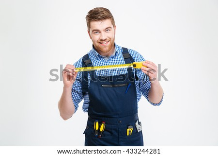 Cheerful attractive young worker in overall smiling and holding measuring tape - stock photo