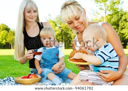 Cheerful babies eating cake outside - stock photo