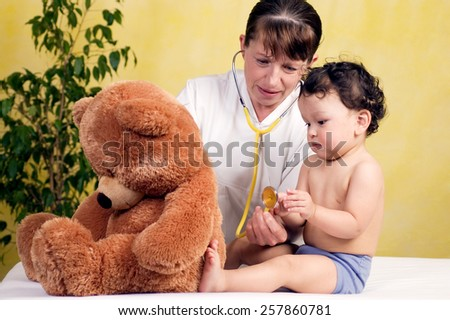 Cheerful baby at the doctor,playing with toy-bear. - stock photo