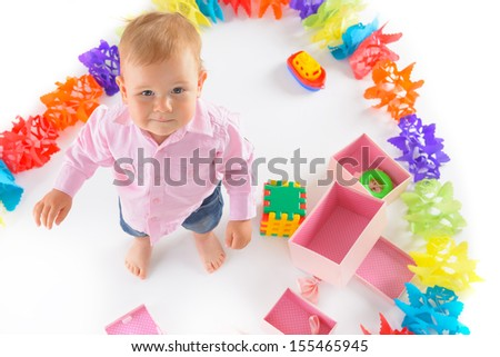 Cheerful baby boy with birthday gifts  over white background