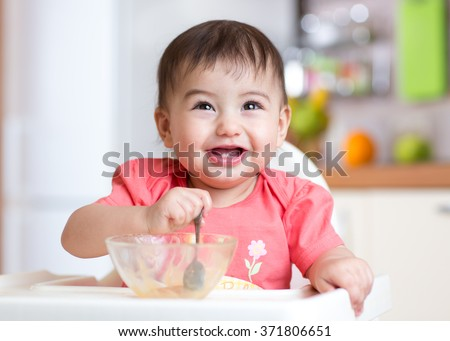 cheerful baby child eating food itself with a spoon - stock photo
