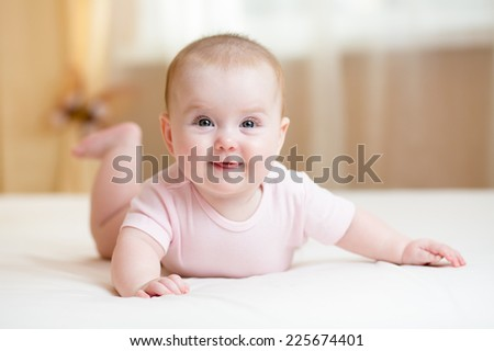 cheerful baby girl lying on white bed indoor - stock photo