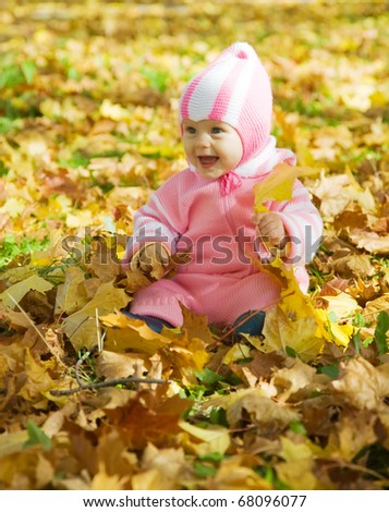 Cheerful baby girl playing with autumnal leaves - stock photo