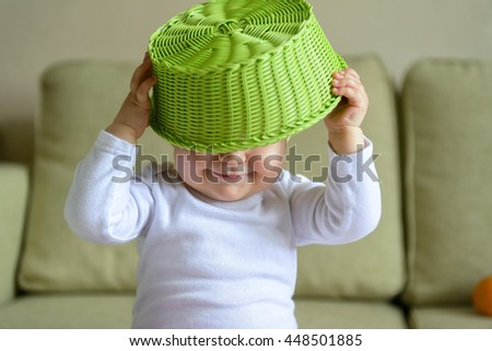 Cheerful baby girl plays with fruit dish at home - stock photo