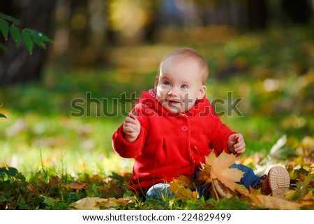 Cheerful baby in a red dress playing with yellow leaves. Child crawls outdoor autumn park. Autumn is time of bright colors. Yellow leaves on the green grass.