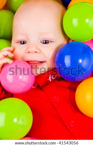 Cheerful baby lying in basin with small colorful balls - stock photo