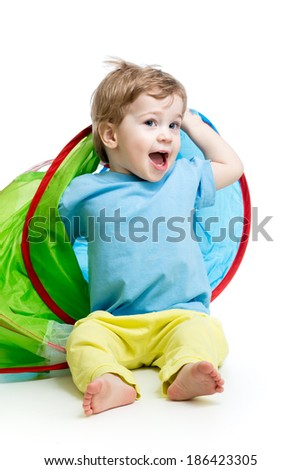cheerful baby playing in a tent - stock photo
