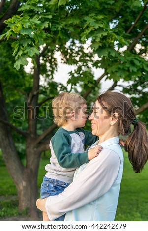cheerful baby playing with mother in the park in the summer. The kid on the hands of the mother. Cheerful little boy playing with his mother in the summer. - stock photo
