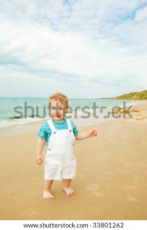 Cheerful baby standing on the beach
