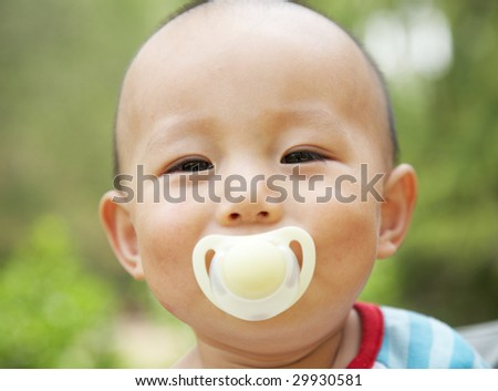 cheerful baby with a pacifier - stock photo